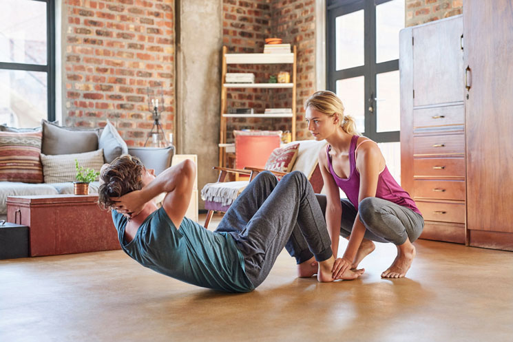Young woman assisting man in doing sit-ups at home. Fit couple is exercising together in living room. Both are in sportswear.